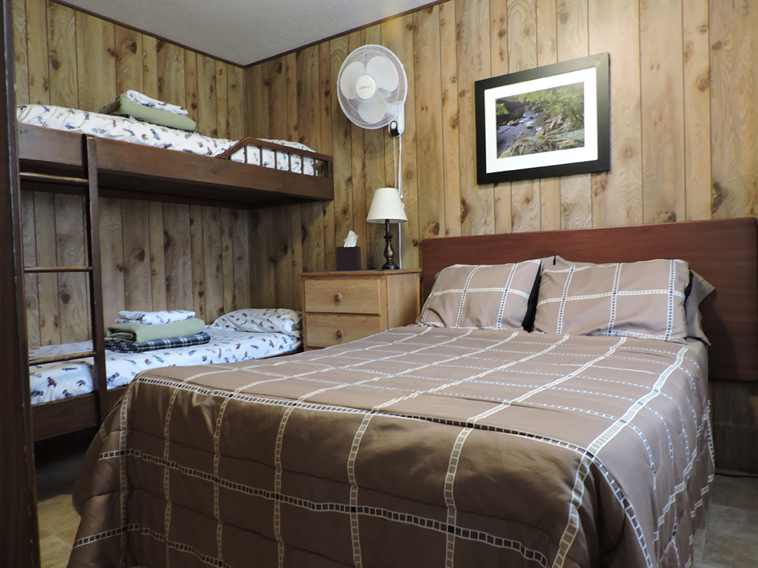 Second bedroom with full-sized bed and twin bunk beds